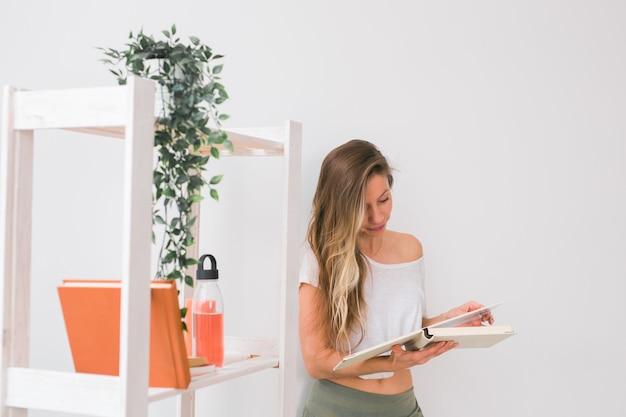 Молодая женщина ищет фотоальбом дома воспоминания и концепция досуга