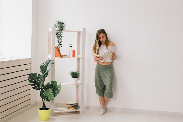 Young woman looking photo album at home memories and leisure concept