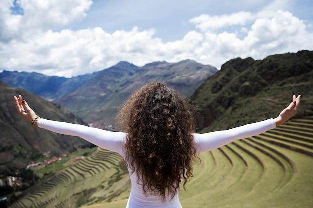 Young woman looking at pisac inca ruins in peru
