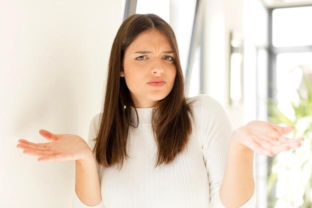 Молодая женщина выглядит озадаченной, смущенной и подчеркнутой, размышляя о разных вариантах, чувствуя себя неуверенно