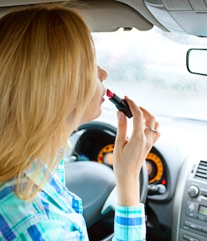 Young woman looking in rear view mirror doing make up.