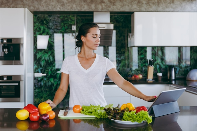 The young woman looking at recipe in laptop in kitchen