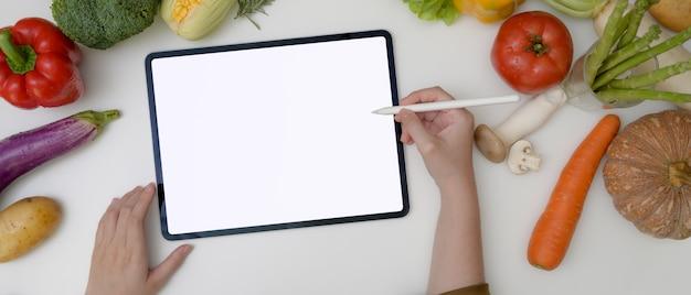 新鮮な野菜の盛り合わせで料理の食材を準備しながら空白の画面のタブレットでレシピを探している若い女性