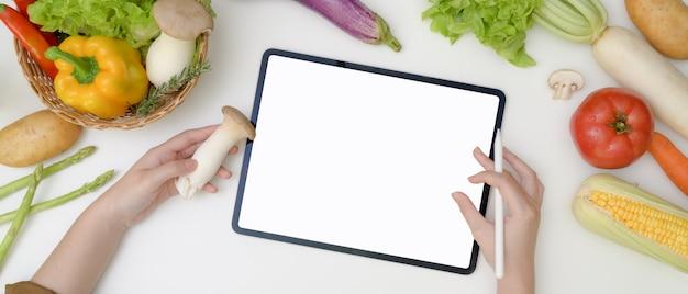 新鮮な野菜と料理の食材を準備しながら空白の画面のタブレットでレシピを探している若い女性