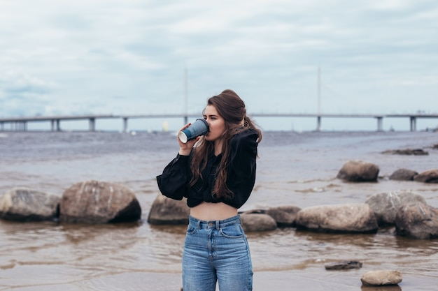 Young woman looking at the sea and drinking coffee