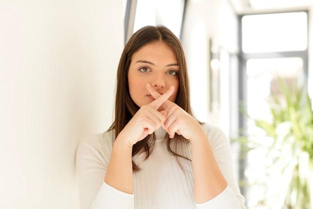 두 손가락으로 심각하고 불쾌 해 보이는 젊은 여성이 침묵을 요구하는 거절로 앞을 넘어 섰습니다.