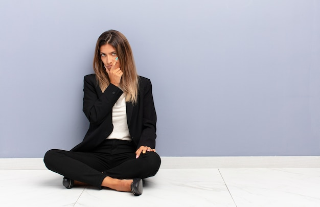 Young woman looking serious, thoughtful and distrustful, with one arm crossed and hand on chin, weighting options business concept