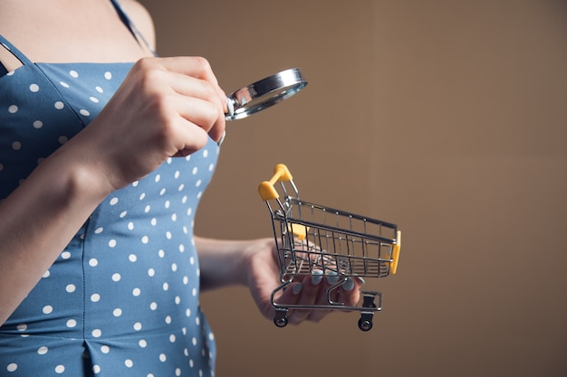 Young woman looking at a shopping cart with a magnifying glass. web search concept