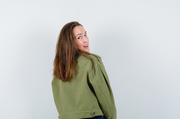 Giovane donna che osserva sopra la spalla in camicia e sembra affascinante. vista posteriore.