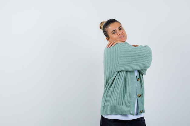 Giovane donna che guarda sopra la spalla in maglietta bianca e cardigan verde menta e sembra attraente