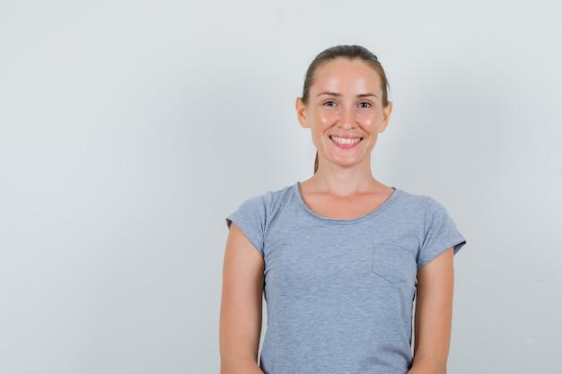Giovane donna alla ricerca e sorridente in maglietta grigia, vista frontale.