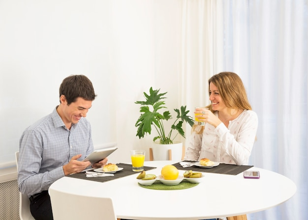 Young woman looking at smiling man using digital tablet at breakfast table