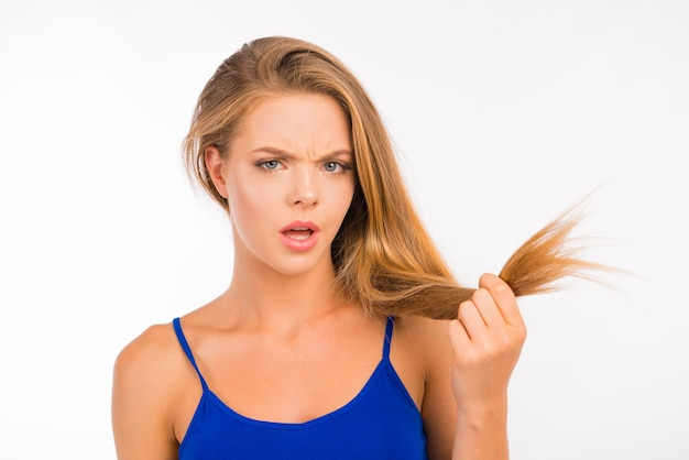 Young woman looking at split ends