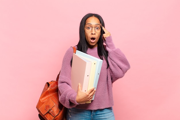 Young woman looking surprised, open-mouthed, shocked, realizing a new thought, idea or concept