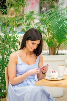 Young woman looking their smartphones while sitting in a cafe. technology people addictions