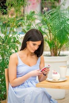 카페에 앉아있는 동안 자신의 스마트 폰을 찾는 젊은 여자. 기술 사람들 중독