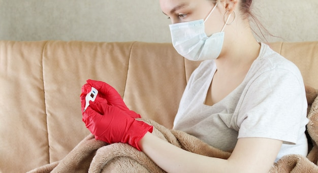 온도계를보고 보호 마스크를 착용하는 젊은 여자, 코로나 바이러스 예방