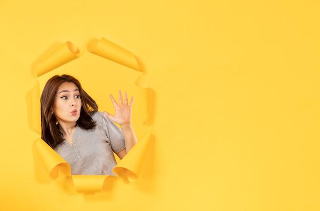 노란색 종이 배경 광고 스파이 창에 구멍을 통해 찾고 젊은 여자