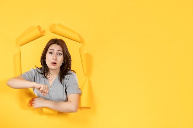 노란 종이 배경 광고 창 모양의 구멍을 통해 보는 젊은 여자