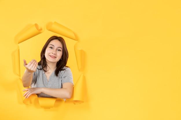 노란 종이 배경 광고 창 스파이의 구멍을 통해 보는 젊은 여자