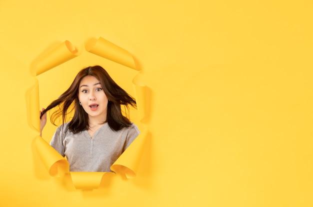 노란 종이 배경 광고 창의 구멍을 통해 보는 젊은 여자