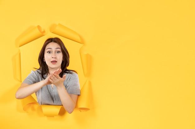 노란 종이 배경의 구멍을 통해 보는 젊은 여성 광고
