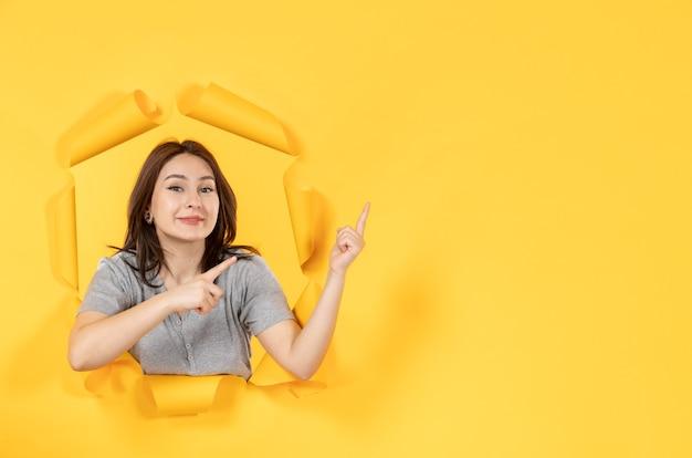 노란 종이 배경의 구멍을 들여다보는 젊은 여성은 창문 광고를 본다