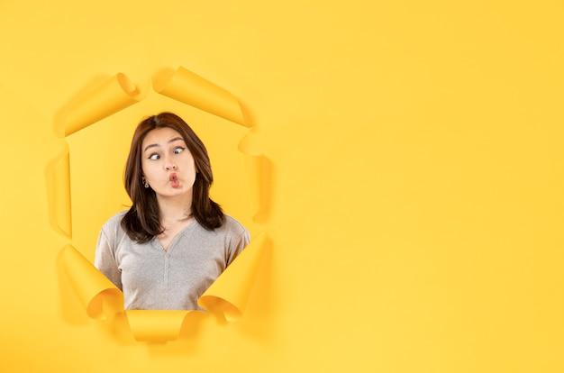 노란색 종이 배경 스파이 광고 창에 구멍을 통해 찾고 젊은 여자