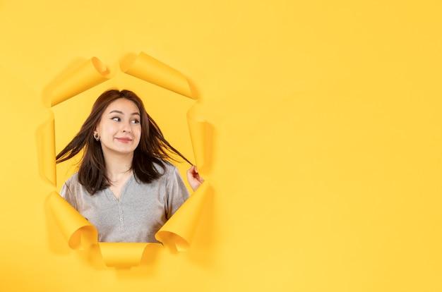 노란 종이 배경 스파이 광고의 구멍을 들여다보는 젊은 여성