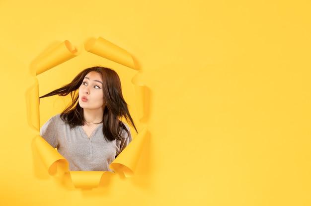 노란 종이 배경 스파이 창에 구멍을 통해 보는 젊은 여자