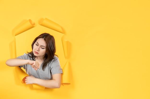 노란 종이 배경 창 광고의 구멍을 통해 보는 젊은 여자