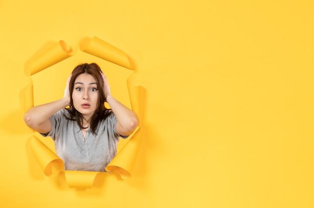 노란 종이 배경 창 모양의 구멍을 통해 보는 젊은 여자