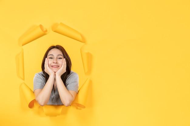 노란 종이 배경 창 스파이의 구멍을 통해 보는 젊은 여자