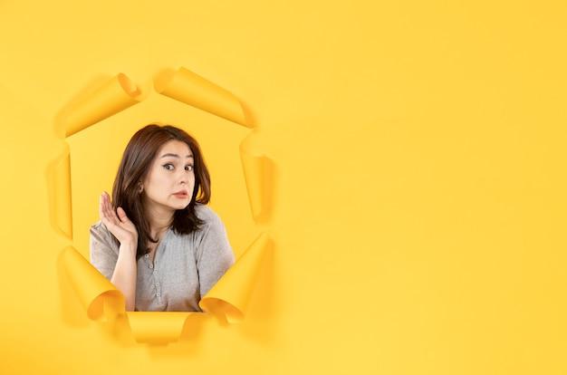 노란색 종이 배경 창 광고 스파이의 구멍을 통해 찾고 젊은 여자
