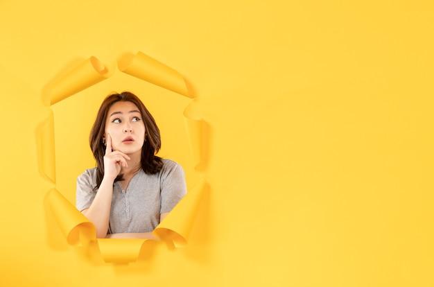 노란색 종이 배경 광고 창 스파이에서 생각하는 구멍을 통해 찾고 젊은 여자