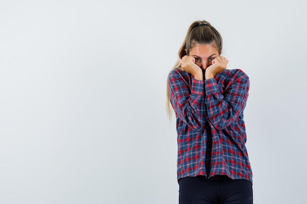 Young woman looking through hands in checked shirt and looking scared