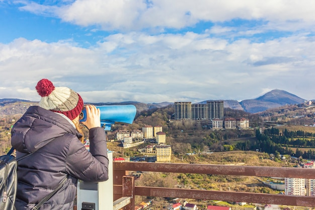 Young woman looking through sightseeing touristic telescope  at the mountains. view from the observation deck (viewing platform). tourist walk, excursion.