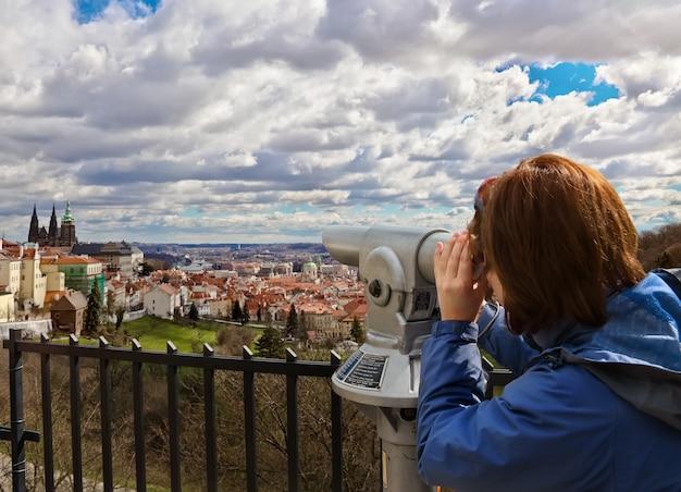 Young woman looking through spyglass at panorama of prague, czech republic