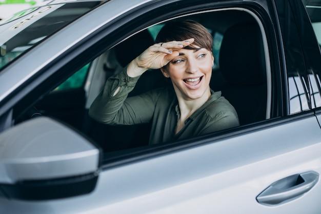 窓の車を通して見ている若い女性