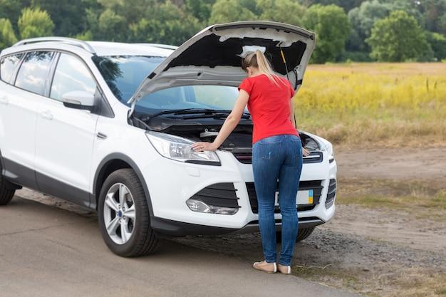 Молодая женщина смотрит под капот разбитой машины на бездорожье