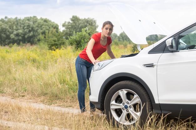過熱した車のボンネットの下を見て若い女性