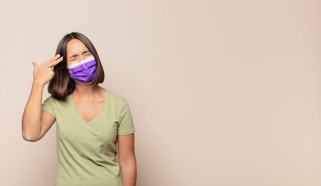 Молодая женщина выглядит несчастной и подчеркнутой, жест самоубийства делает знак пистолет рукой, указывая на голову