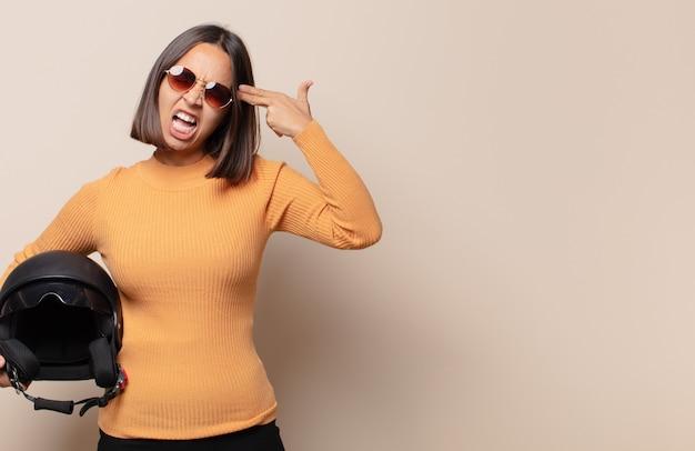 Молодая женщина выглядит несчастной и подчеркнутой, жест самоубийства делает знак пистолета рукой, указывая на голову