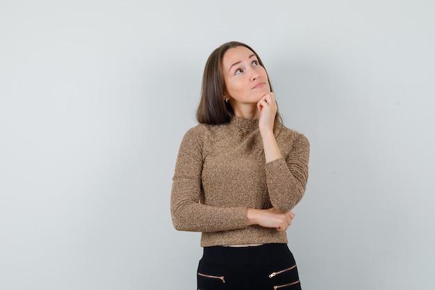 Молодая женщина, глядя вверх в золотой блузке