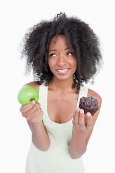 果物とチョコレートの間で選択する助けを求めるために探している若い女性