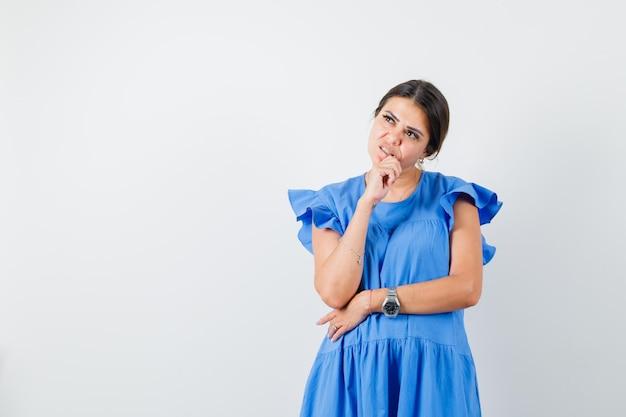Молодая женщина смотрит вверх с рукой на подбородке в синем платье и смотрит задумчиво
