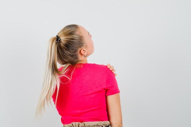 ピンクのtシャツの肩に触れて、集中して見える手で見上げる若い女性