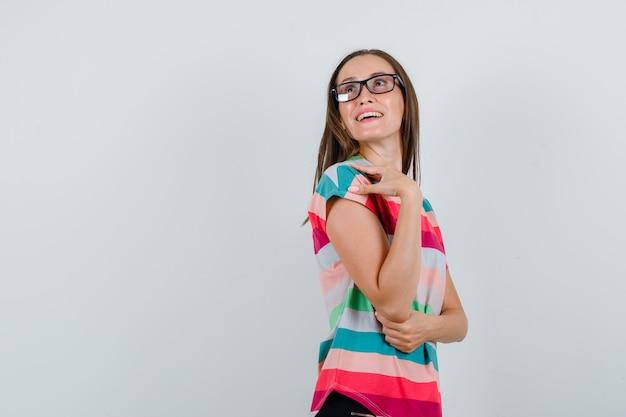 Молодая женщина смотрит вверх в футболке, штанах, очках и смотрит с надеждой, вид спереди.