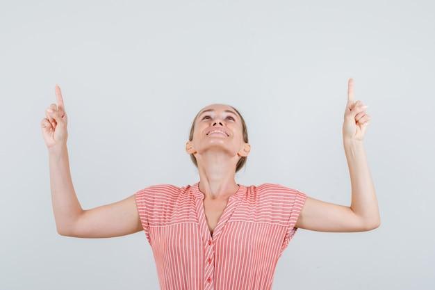 Молодая женщина смотрит вверх с пальцем в полосатом платье и выглядит веселой, вид спереди.