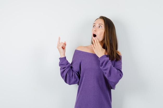 Молодая женщина смотрит вверх с пальцем в фиолетовой рубашке и смотрит удивленно, вид спереди.